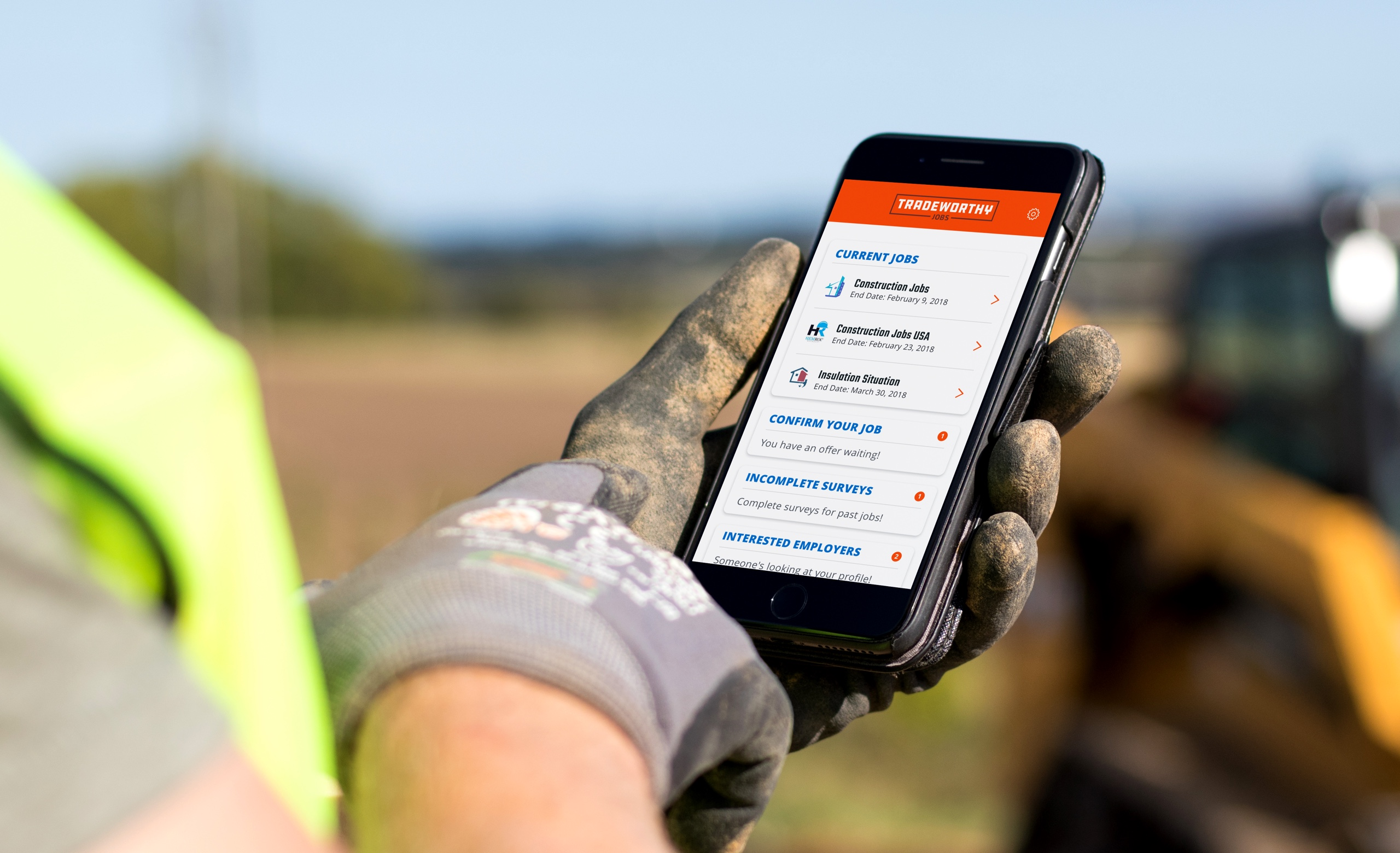 Construction worker on a construction site holding a cellphone with the Tradeworthy Jobs app pulled up on it.