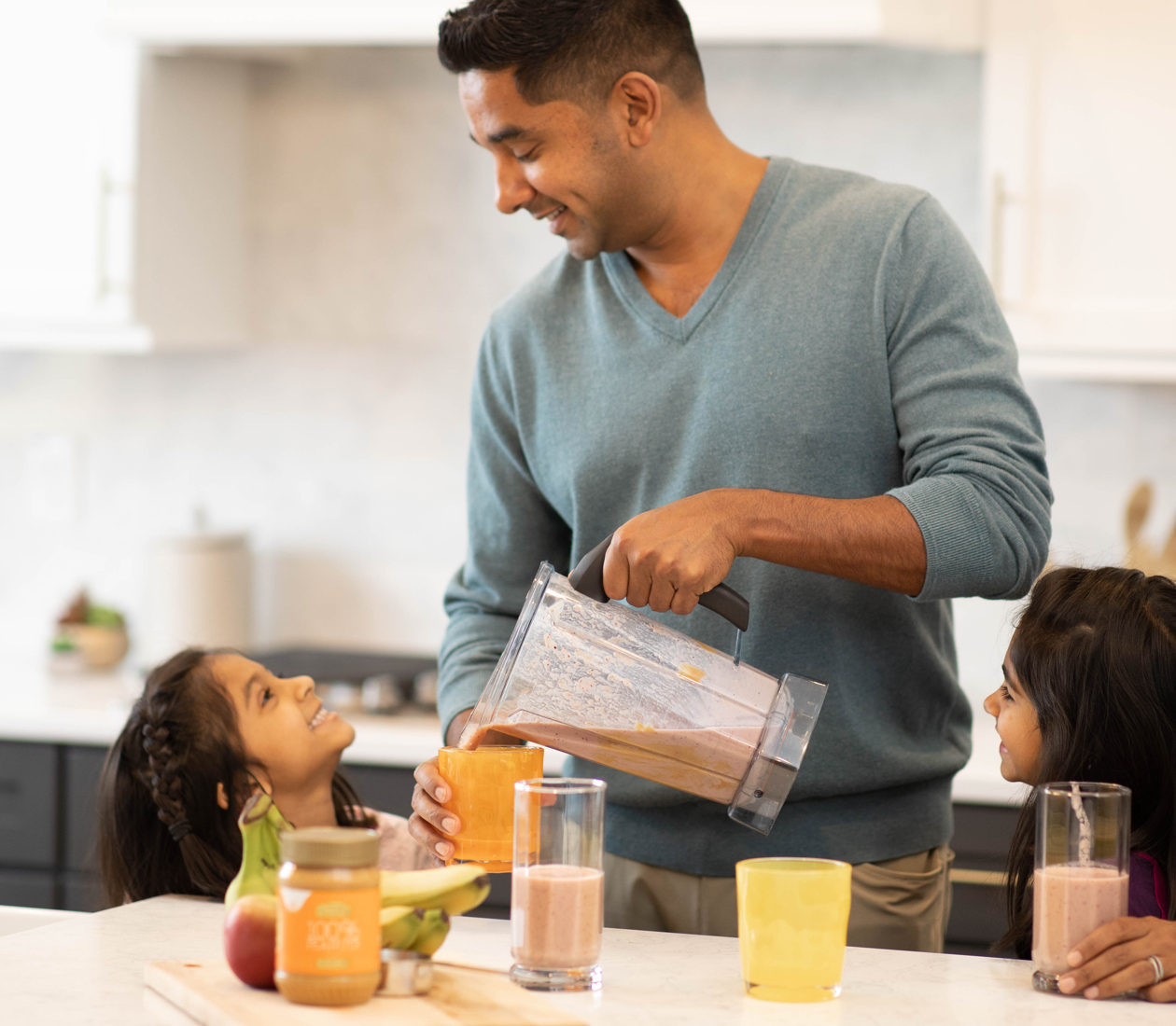 A father pouring a peanut butter smoothie for his daughter